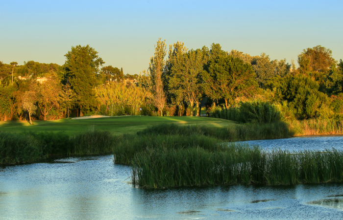 Dom Pedro Laguna Golf Course surrounded by trees and water