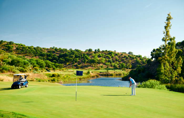 Player hitting a ball in a green of the Monte Rei Golf Course