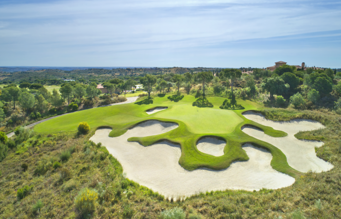 Green in the Monte Rei golf course surrounded by sand bunkers