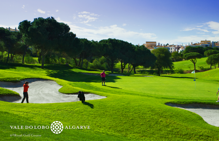 Golfer playing the ball in a green side bunker in Vale do Lobo Royal