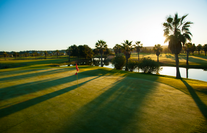 Green of Salgados golf course with flagstick and lake on the right side