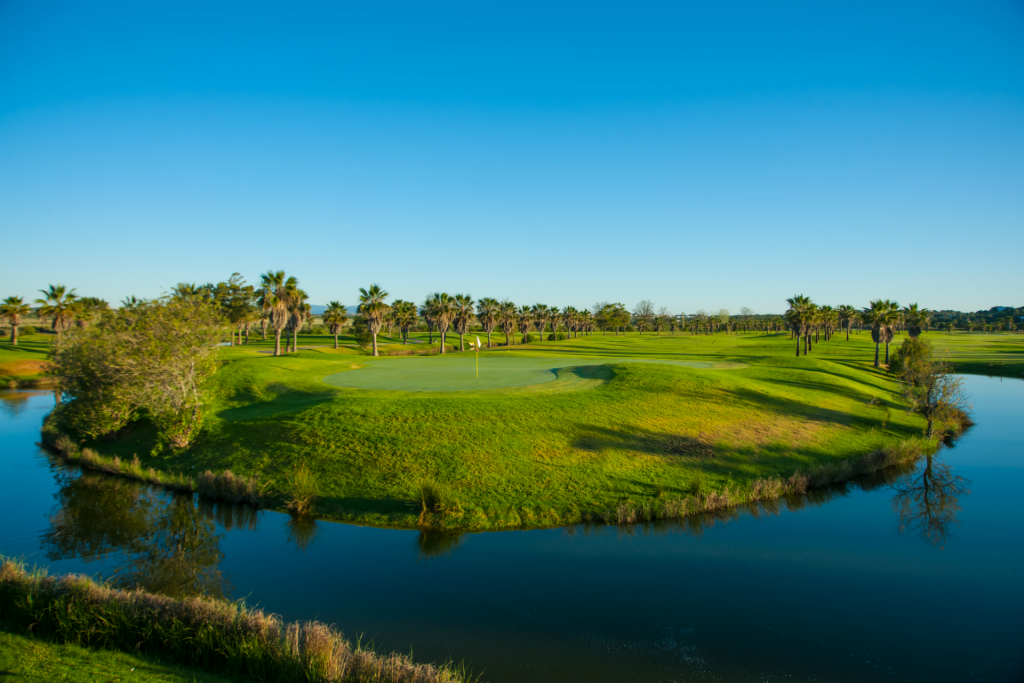 Green of Salgados Golf Course surrounded by water