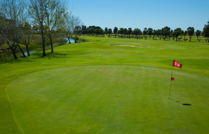 Green of Salgados Golf Course with lake on the left side